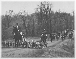 Major Harry Brown, honorary huntsman, leading the Rocky Fork hounds down the Rocky Fork Hunt and Country Club driveway, in 1934. The Hunt's stables appear on the hill in the background.