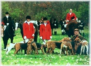Blessing of the Hounds in the late 1980s. MFHs Lynne Ashbrook and Cynthia Jeffrey are shown on foot accompanied by kennelman Junior Burgess. Mounted in the background are Amy Ashbrook Comisford, then a whipper-in who later became an MFH, and Col. Walter Morgan, whipper-in.
