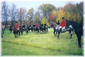 A lull in the hunting action in the mid-1990s, taken in the back of Carlin's house in the Jersey territory. Identifiable members are Bill Dreger in red on the gray, Col. Walter Morgan in red on the chestnut, Dr. Michael Fraley on the clipped bay, Stan Shayne in red next to Elaine Shayne and Kate Rigg all on bays, Sharon Chappelear (side view) on the chestnut and Jim Thorson on the Appaloosa.